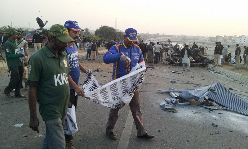 Photo shows rescue workers at the site of the blast that killed senior police officer Chaudhary Aslam in Karachi, Jan 9, 2014.—Photo by Asif Mehmood