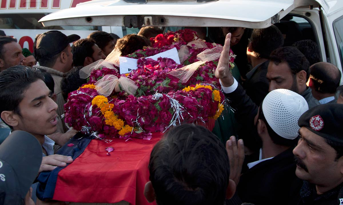 People load coffin containing the body of police investigator Chaudry Aslam in Karachi, Jan 10, 2014. — AP
