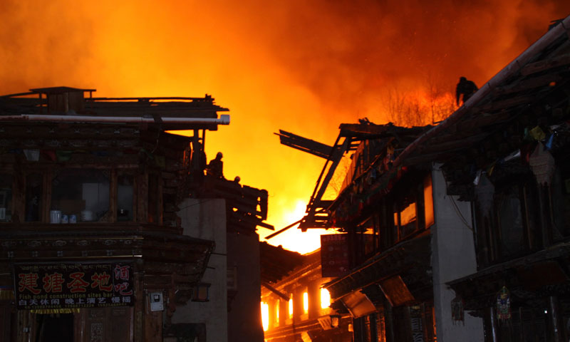 Firefighters work on roofs of buildings while a fire ravages ancient Dukezong town in Shangri-la county, in southwestern China's Yunnan province, Saturday, Jan 11, 2014. — Photo by AP