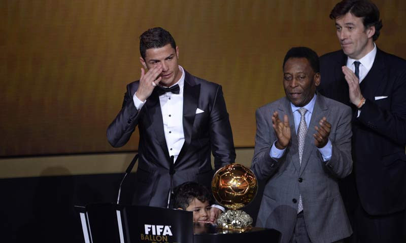 Brazilian football legend Pele (R) applauds next to Real Madrid's Portuguese forward Cristiano Ronaldo as he cries after receiving the 2013 FIFA Ballon d'Or award for player of the year during the FIFA Ballon d'Or award ceremony at the Kongresshaus in Zurich. -AFP Photo