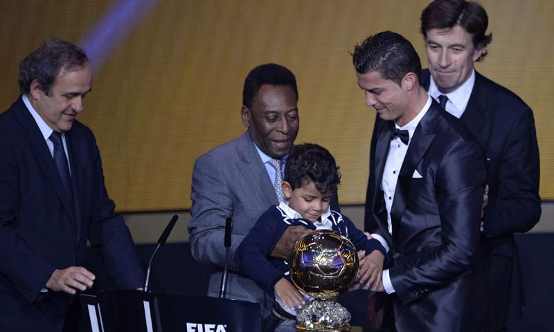 Real Madrid's Portuguese forward Cristiano Ronaldo (front-R) holds the 2013 FIFA Ballon d'Or award for player of the year with his son Cristiano Ronaldo Junior after receiving it from Brazilian football legend Pele (C) next to UEFA president Michel Platini (L) and France Football president Francois Moriniere (back-R) during the FIFA Ballon d'Or award ceremony at the Kongresshaus in Zurich. -AFP Photo