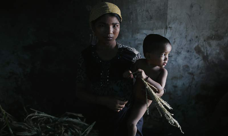 A Rohingya Muslim woman displaced by violence, holds her one-year-old daughter at a former rubber factory that serves as their shelter in Myanmar. -Reuters/File Photo