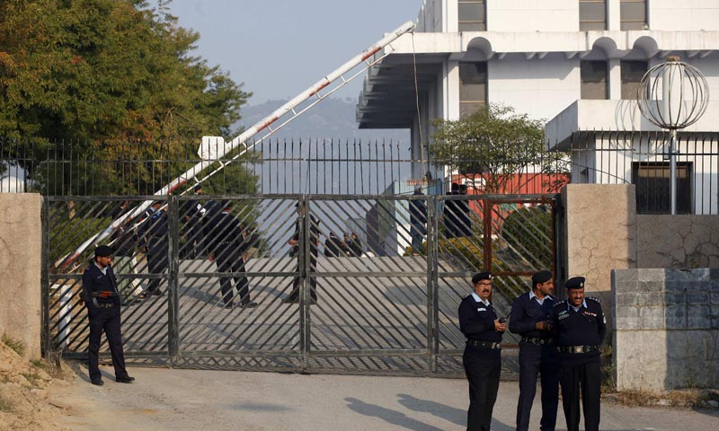 Police officers stand guard at the gate of the special court, formed to try Pervez Musharraf for treason in Islamabad. — Photo by Reuters