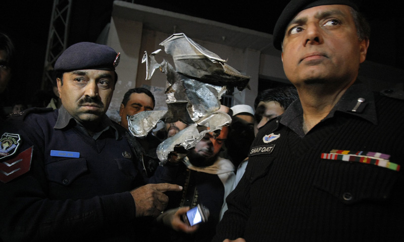 Pakistani police officers show the remains of explosive container outside a seminary in Peshawar, Thursday, Jan. 16, 2014. – AP Photo