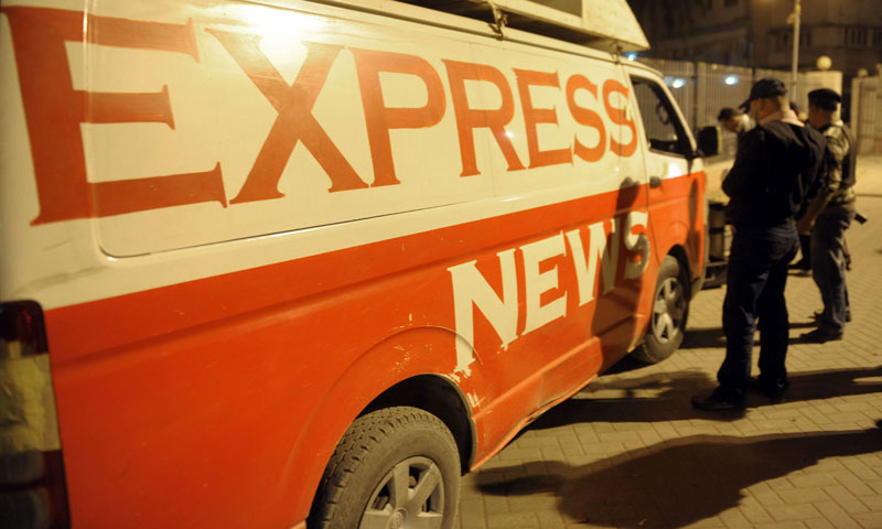 Security officials inspect a DSNG (digital satellite news gathering) vehicle of a private news channel following an attack by gunmen in Karachi late on January 17, 2014. — Photo by AFP