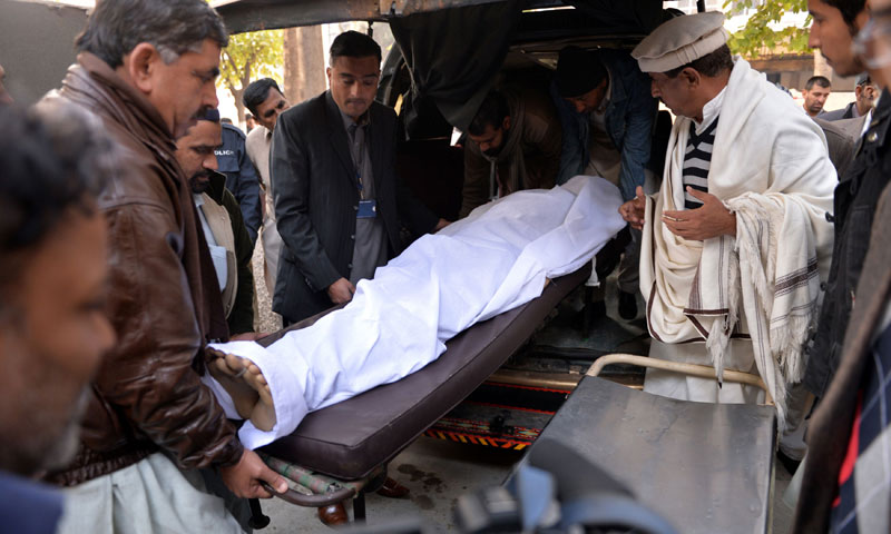 Volunteers and relatives move the body of victim of a suicide bomb attack, at a hospital in Rawalpindi on January 20, 2014. — Photo by AFP