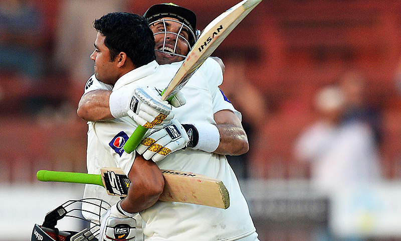Azhar Ali (R) celebrates after scoring his match-winning century with captain Misbah-ul-Haq. -Photo by AFP
