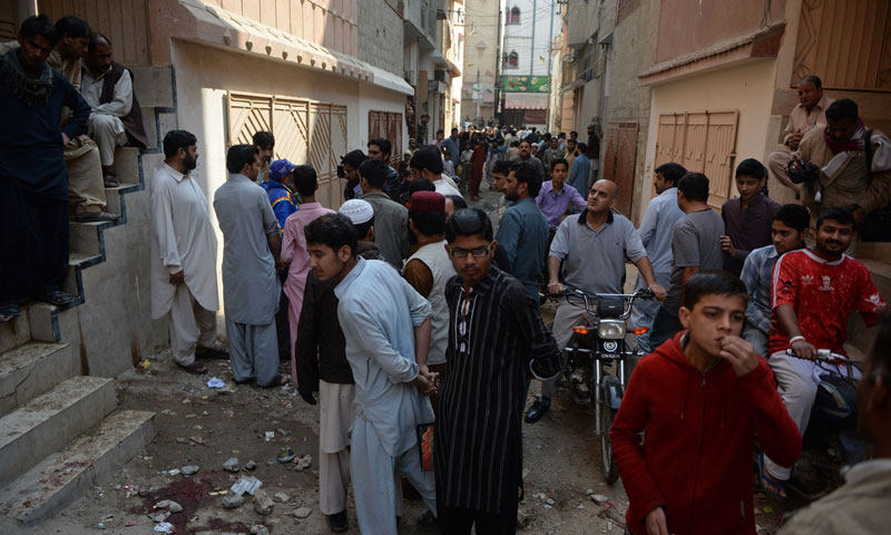 Residents gather at the site of a gunmen attack on health workers in Karachi on January 21, 2014. — Photo by AFP