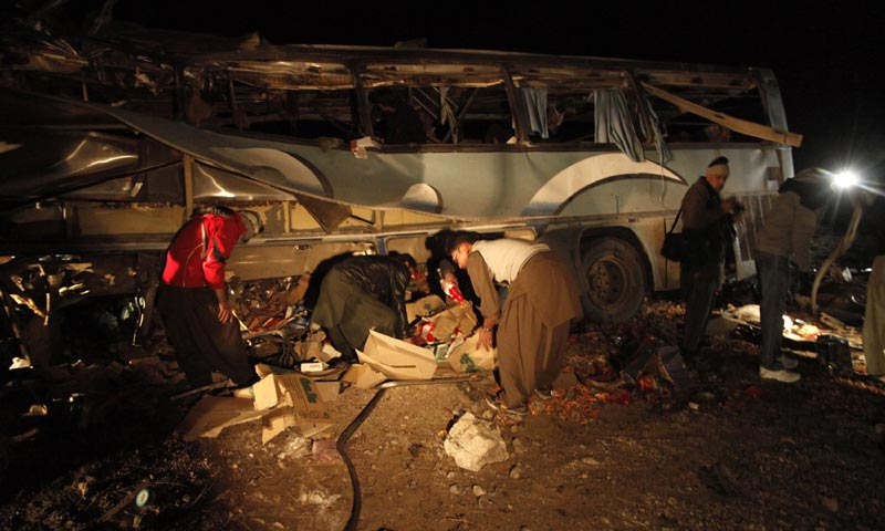 Rescue workers collect evidence from a burnt passenger bus on the outskirts of Quetta. -Reuters Photo
