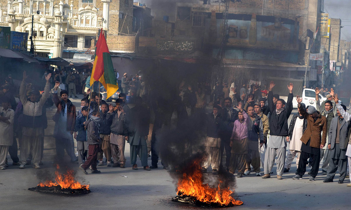 Pakistani Shiite Muslim mourners chant slogans as they gather at burning tyres near the coffins of victims of an overnight bombing of a bus, during a protest in Quetta on January 22, 2014. –Photo by AFP