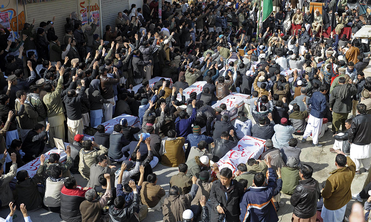 Hundreds sit beside coffins during a protest in Quetta, bearing the remains of those killed in the Mastung bus bombing, on January 22, 2014.—AFP