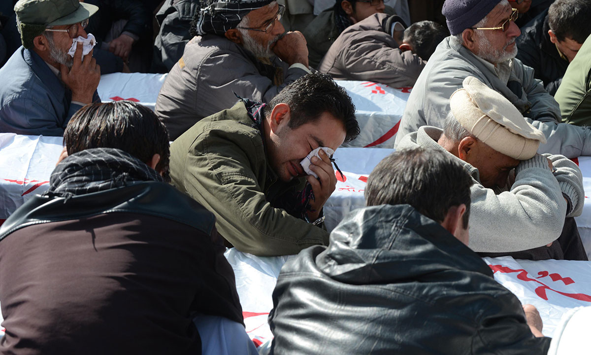 Pakistani Shiite Muslims mourn beside coffins, bearing the remains of those killed in an overnight bombing. – Photo by AFP