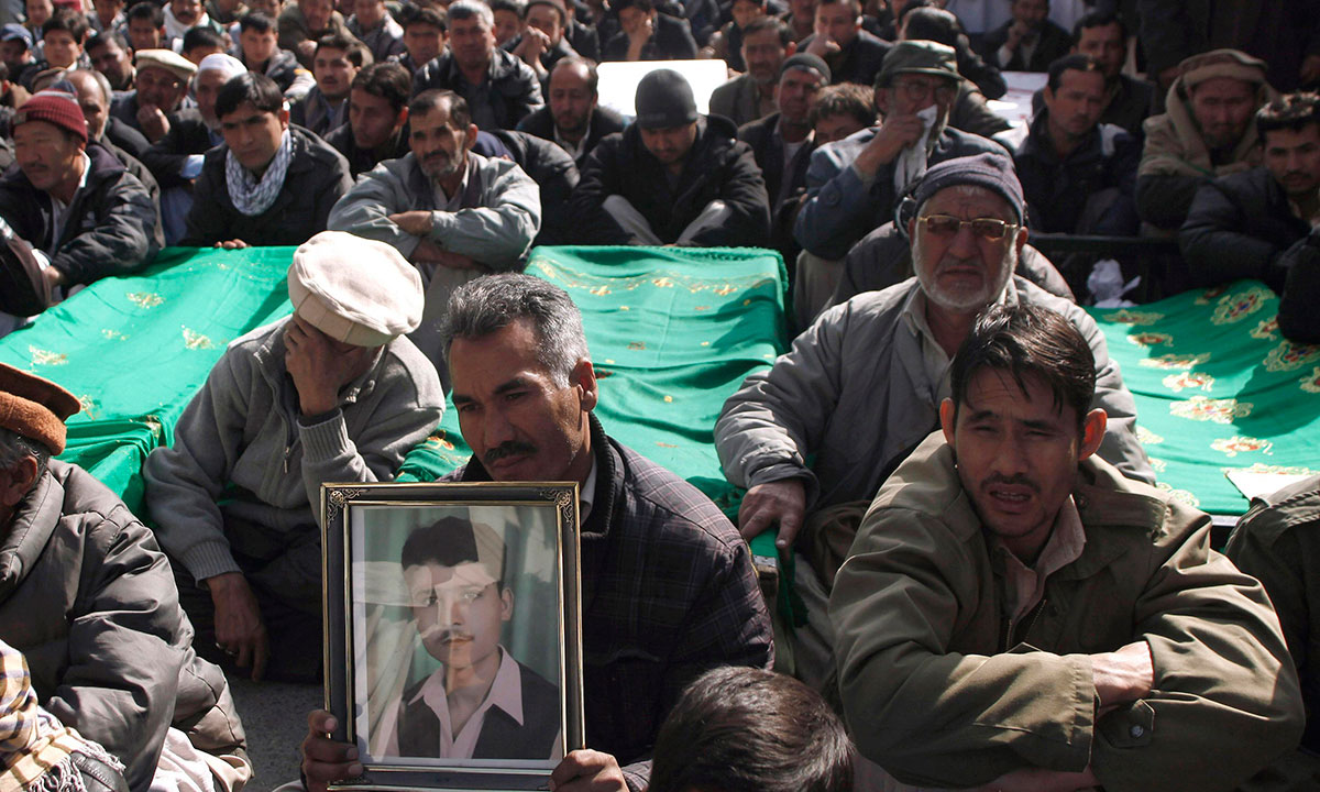 A Shi'ite Muslim man holds a picture of his relative as he sits beside the covered bodies of other victims who were killed in Tuesday's night bomb attack on a bus, during a protest in the provincial capital of Quetta January 22, 2014. – Photo by Reuters
