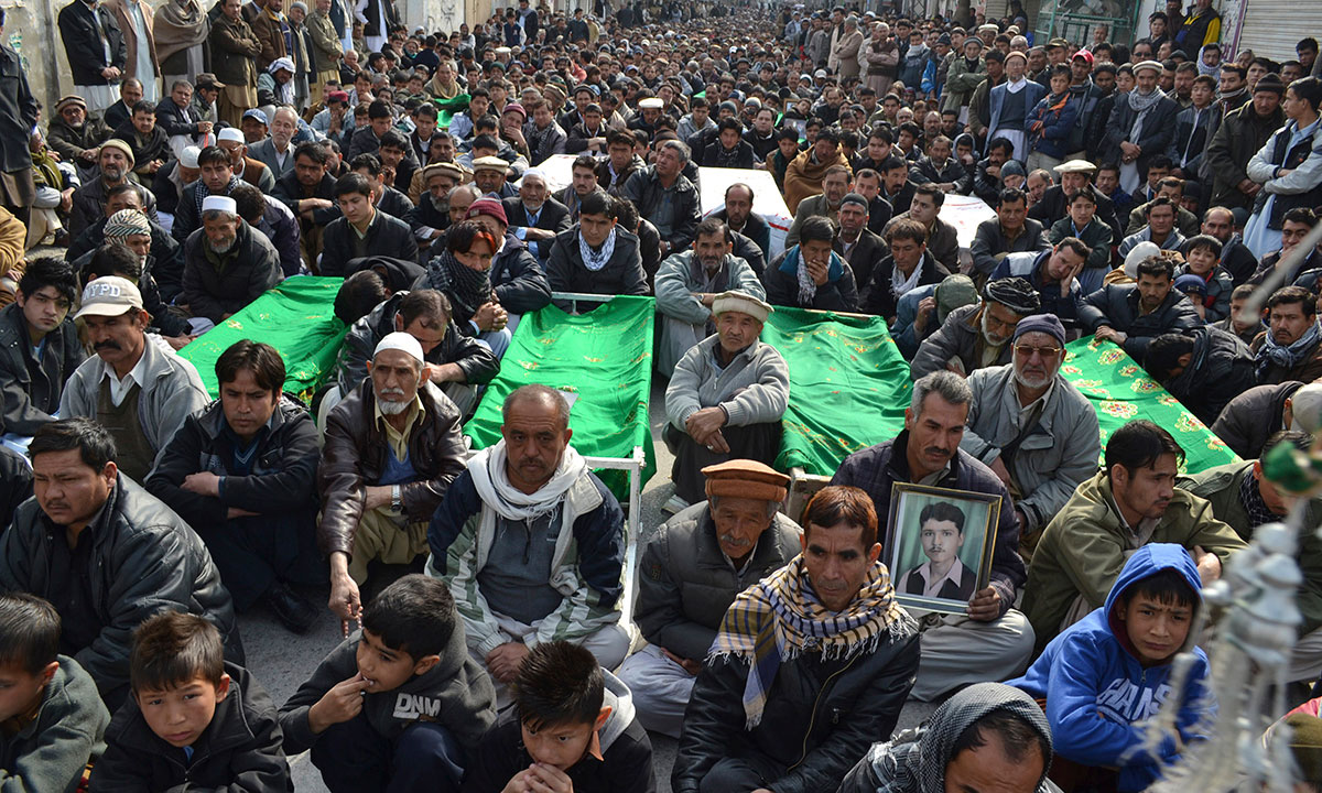 Relatives and mourners of  Shiite pilgrims who were killed on Tuesday by a bomb blast, protest sitting next to their bodies, in Quetta, Pakistan. – Photo by AP