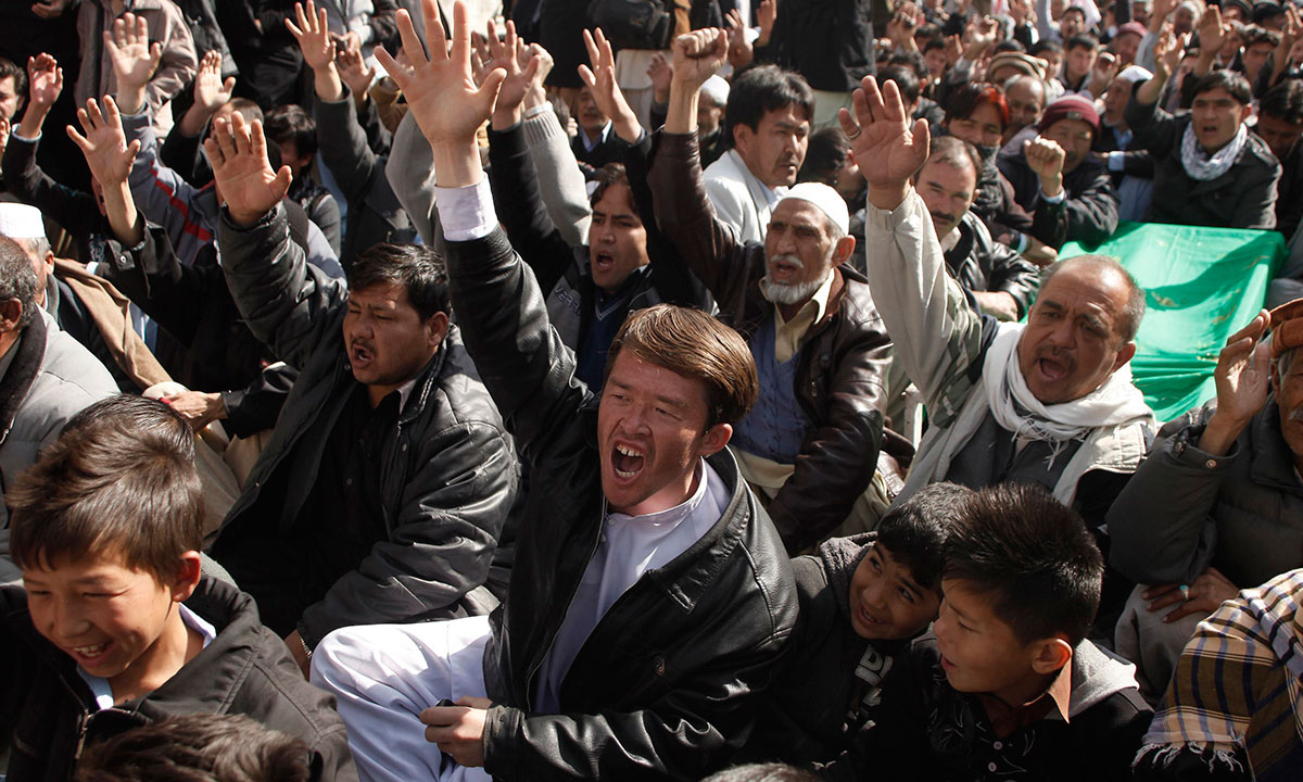 Shi'ite Muslims shout slogans as they sit beside the covered bodies of those who were killed in Tuesday night's bomb attack on a bus, during a protest in the provincial capital of Quetta. – Photo by Reuters