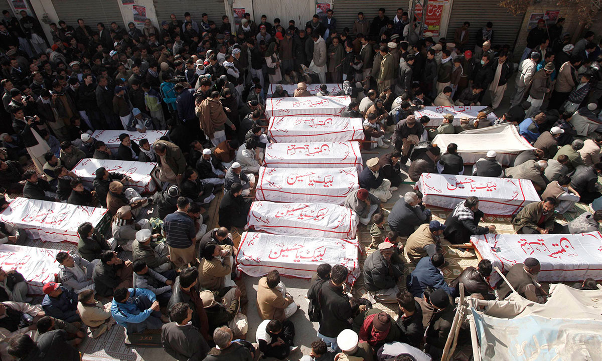 Shi'ite Muslims sit beside the covered bodies of victims who were killed in Tuesday night's bomb attack on a bus, during a protest in the provincial capital of Quetta. – Photo by Reuters