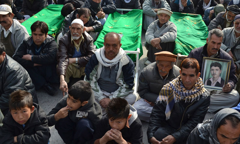 Relatives and mourners of  Shia pilgrims who were killed on Tuesday by a bomb blast, protest sitting next to their bodies, in Quetta, Wednesday, Jan. 22, 2014.—AP Photo