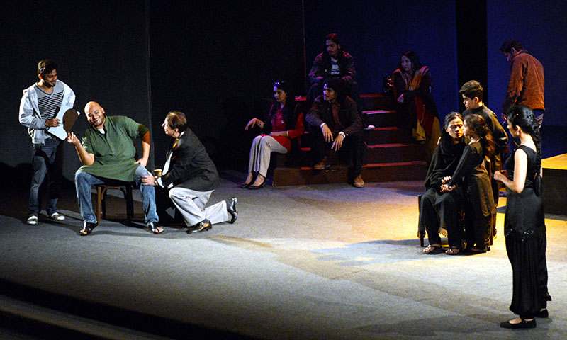 The father (Rahat Kazmi, on his knees) imploring the director (Hammad Sartaj, in the chair) to use him and members of his family as characters. – Photo by White Star