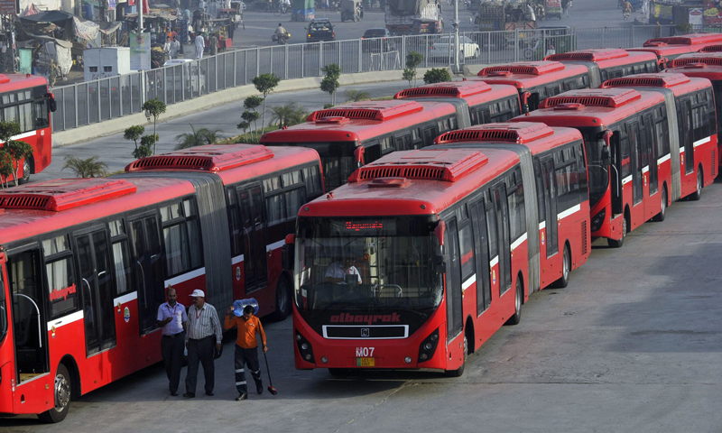 This photograph taken on June 5, 2013, shows employees walking beside metro buses parked at a terminal in Lahore. — AFP Photo