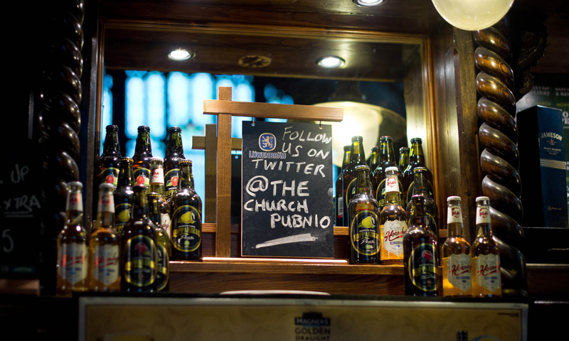 A sign promoting a twitter account is placed inside O'Neills pub built in a former Presbyterian church in Muswell Hill, north London.