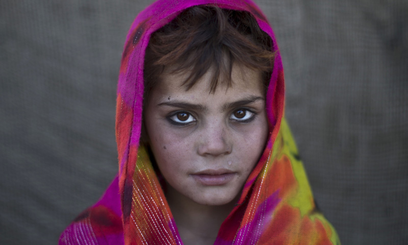 An Afghan refugee girl, Nazmina Bibi, 7, poses for a picture, while playing with other children in a slum on the outskirts of Islamabad. — Photo by AP