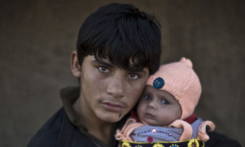 Afghan refugee youth, Shahzada Saleem, 15, holds his nephew Satara, two months, as they pose for a picture, in a slum on the outskirts of Islamabad, Pakistan. — Photo by AP