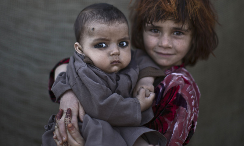 Afghan refugee girl, Khalzarin Zirgul, 6, holds her cousin, Zaman, three months, as they pose for a picture, while playing with other children in a slum on the outskirts of Islamabad, Pakistan, Monday, Jan 27, 2014. — Photo by AP