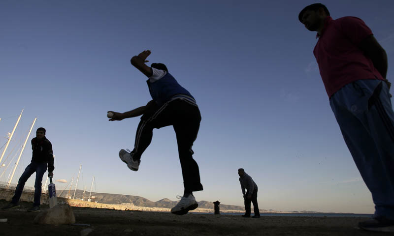 Pakistanis play cricket on Freatida beach after finishing work in nearby businesses in Piraeus port, near Athens on Wednesday, Jan. 29, 2014. – AP Photo
