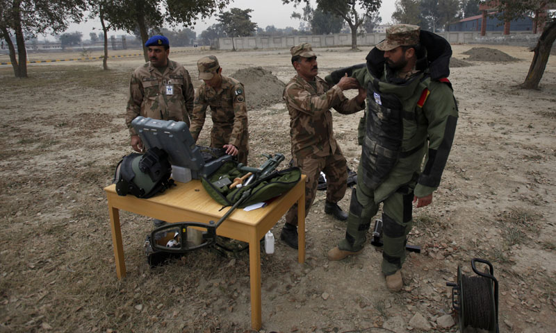 In this Wednesday, Jan. 8, 2014, photo, A Pakistani soldier helps his colleague to put on a bomb suit for a training session at the Counter IED Explosives and Munitions School, in Risalpur, Pakistan.— Photo by AP