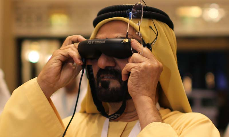United Arab Emirates' Prime Minister and Ruler of Dubai Sheikh Mohammed bin Rashid al-Maktoum looks through a visor as he tests an unmanned aerial drone during Virtual Future Exhibition, in Dubai February 9, 2014. The United Arab Emirates says it plans to use unmanned aerial drones to deliver official documents and packages to its citizens as part of efforts to upgrade government services. Picture taken February 9, 2014.  REUTERS/Ahmed Jadallah (UNITED ARAB EMIRATES - Tags: BUSINESS SCIENCE TECHNOLOGY ROYALS POLITI
