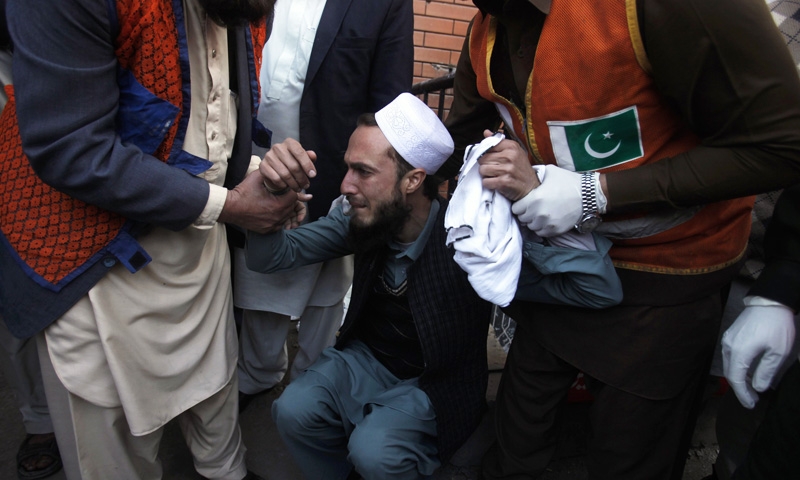Rescue worker comfort a man over the death of his brother who died in a grenade attack at the Lady Reading Hospital in Peshawar February 11, 2014. – Reuters Photo