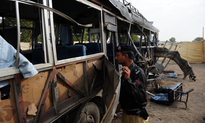 A policeman inspects the wreckage of a police bus at the site of a bomb attack in Karachi on February 13, 2014. — Photo by AFP