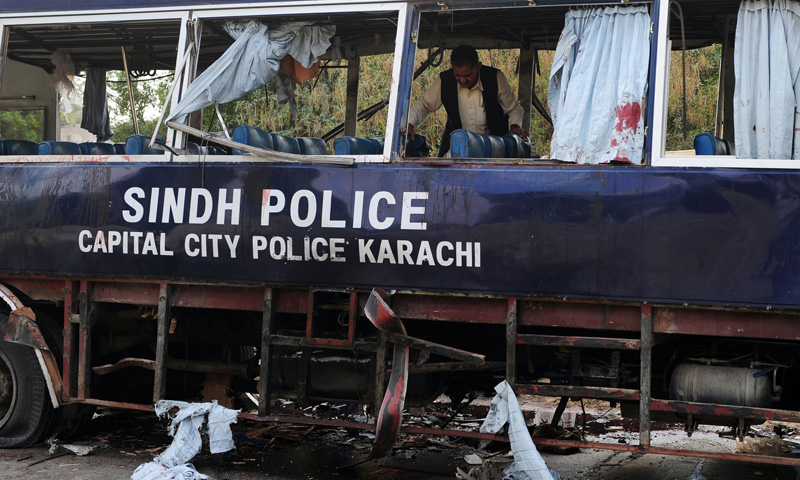 A policeman inspects a damaged police bus at the site of a bomb attack in Karachi on February 13, 2014.— Photo by AFP
