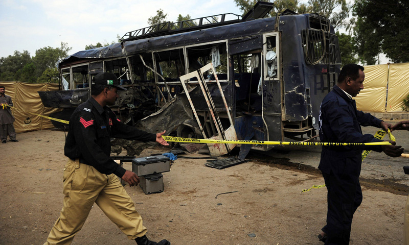 Policemen cordon off the wreckage of the police bus at the site of a bomb attack in Karachi on February 13, 2014. — Photo by AFP