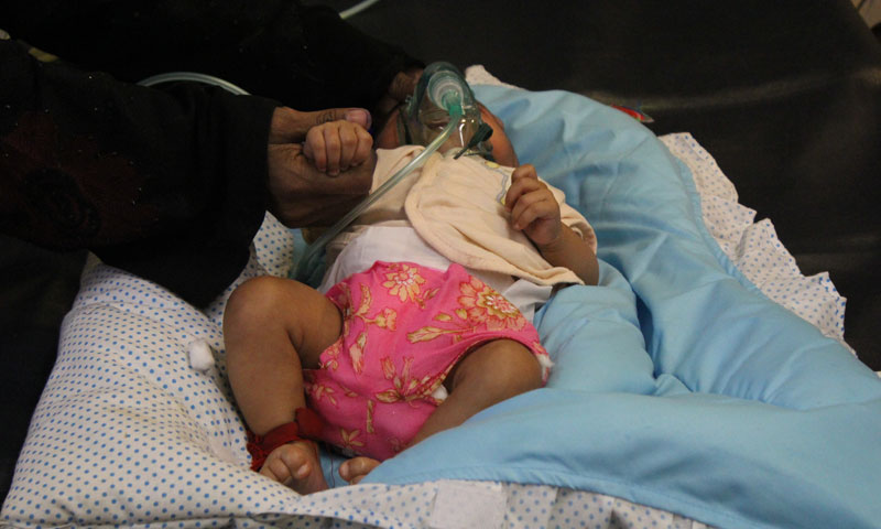 A mother trying to comfort her baby girl while she is treated in the intensive care unit at NICH. -Photo by Asif Umar.
