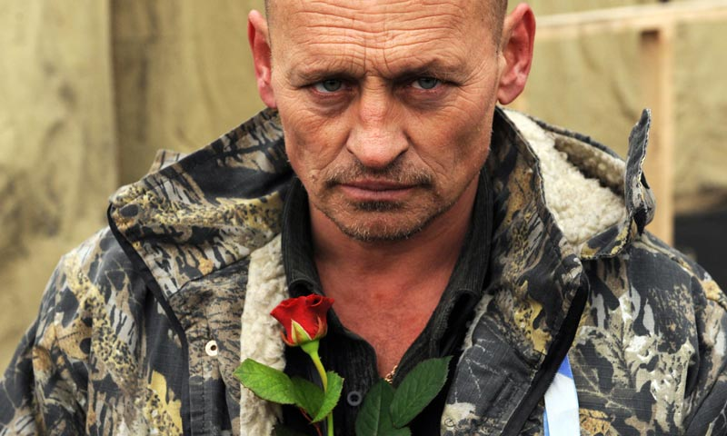 A man brings a rose to a memorial to the anti-government protesters killed durign the past weeks' clashes with riot police in Kiev's Independence Square. -AFP Photo