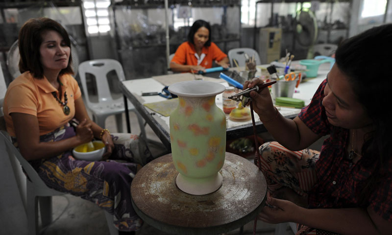 This picture shows Thai widows working at a clay pots workshop at the army-protected state 'widows' village' of Rotan Batu. — Photo by AFP