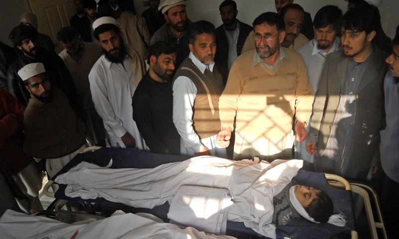 Relatives and mourners of a boy who was killed in a bomb blast gather around his body at a hospital in Kohat, Pakistan, Sunday, February 23, 2014. — Photo by AP