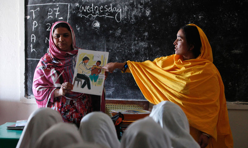 Teachers display a card with an illustration depicting a girl going through a medical checkup by a doctor, as they describe preventive measures to avoid when sexual harassment occurs, during a class in Shadabad Girls Elementary School in Pir Mashaikh village in Johi, some 325 km (202 miles) from Karachi. — Photo by Reuters
