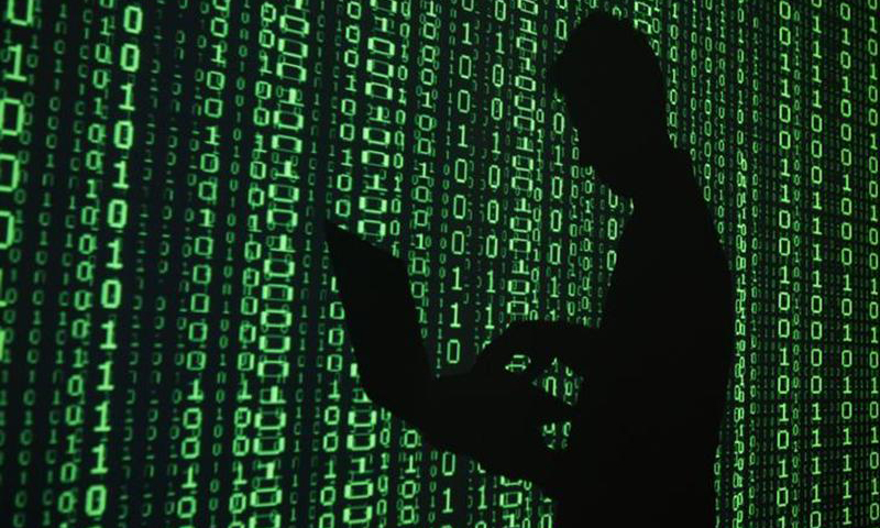 An illustration picture shows a projection of binary code around the shadow of a man holding a laptop computer in an office in Warsaw June 24, 2013. — Reuters Photo