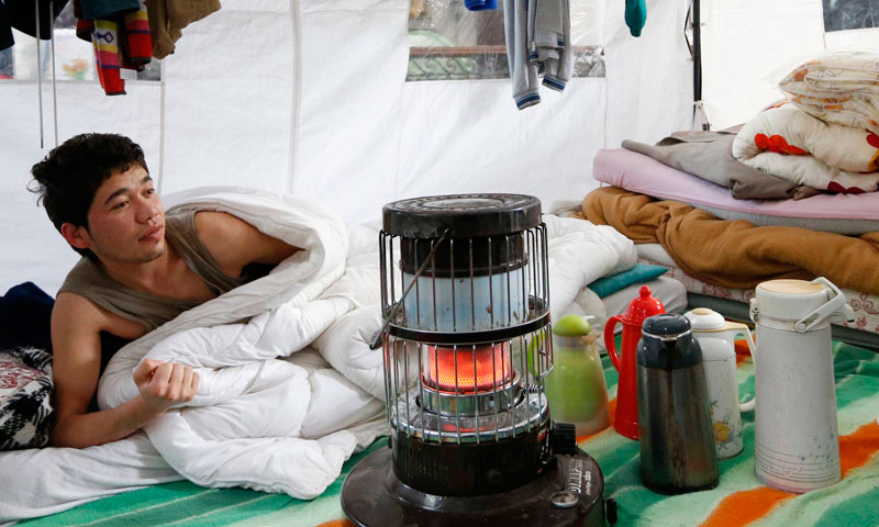 An Afghan asylum seeker wakes up near a stove after a night inside a tent at the Church of Saint John the Baptist at the Beguinage in central Brussels.
