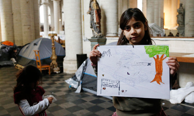 Hadiha Homahi, 8, from Afghanistan, displays her drawing inside the Church of Saint John the Baptist at the Beguinage in central Brussels.