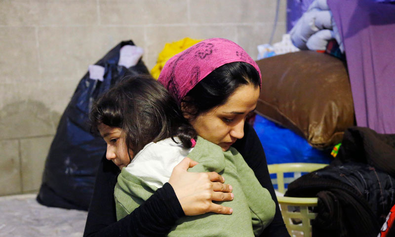 Khatera Shams from Kabul, Afghanistan, consoles her daughter Hadia, 5, as they sit in a tent at the Church of Saint John the Baptist at the Beguinage in central Brussels.