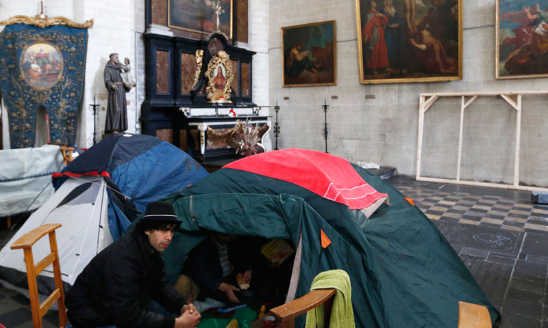 An asylum seeker from Afghanistan sits near tents at the Church of Saint John the Baptist at the Beguinage in central Brussels.