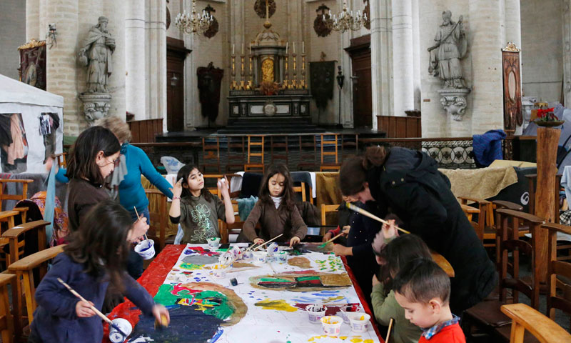 Afghan children take part in a drawing workshop inside the Church of Saint John the Baptist at the Beguinage in central Brussels.