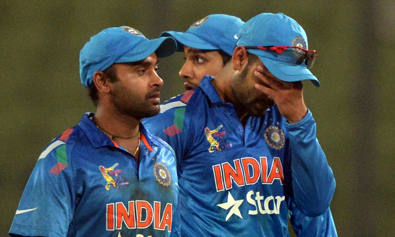 Indian captain Virat Kohli (R) with teammates returns to the dressing room after losing the match against Pakistan in Dhaka on March 2, 2014. – AFP
