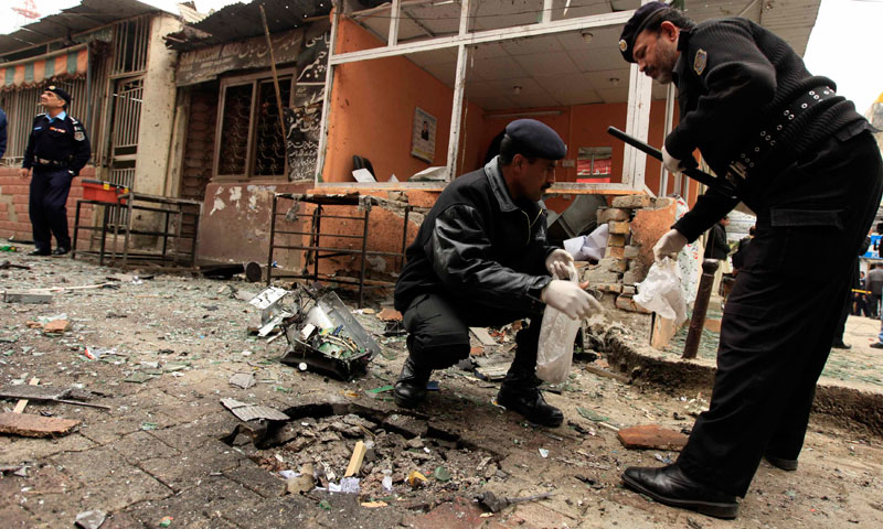Policemen collect evidence from the site of a bomb attack at the district court in Islamabad, March 3. — Photo by Reuters