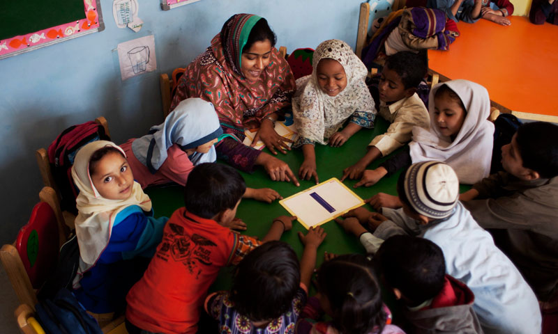 Students gather around Humaira Bachal, the founder of a charity school as she teaches them in a classroom in Karachi, Pakistan.— Photo by AP