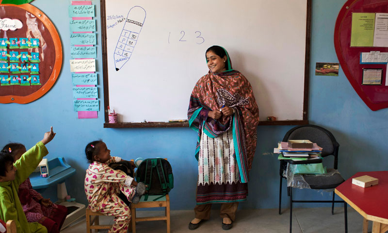 Humaira Bachal, the founder of a charity school, speaks with students in a classroom in Karachi. — Photo by AP