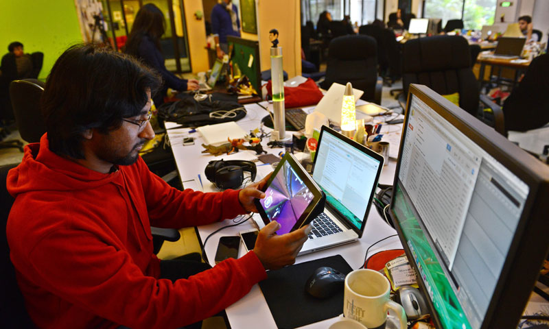 Pakistani game designer Waqar Azim checks a designed game at his workplace in Islamabad. — Photo by AFP